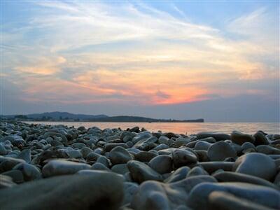 Západ slunce nad kamennou pláží
